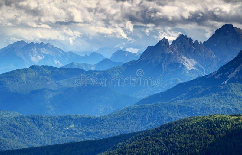 Bläulicher Nebel und dunkle Wolken über bewaldeten Kanten Dolomiti Italien lizenzfreies stockbild