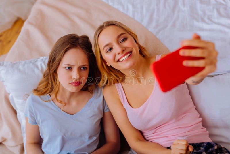 Blåögd borrad systerkänsla, medan göra fotoet med äldre sibling royaltyfri fotografi