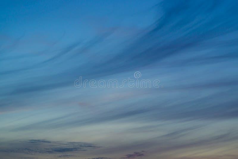Blå aftonhimmel med den suddiga solen på horisonthostaketet Idérik idé underexponerat foto royaltyfri bild