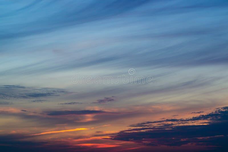 Blå aftonhimmel med den suddiga solen på horisonthostaketet Idérik idé underexponerat foto blå timme royaltyfri bild