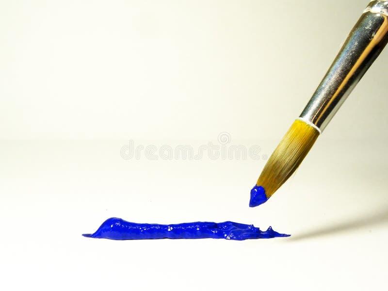 Blå akrylmålarfärg på borsten och på ett ark av papper arkivfoton