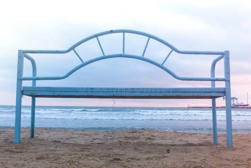 Blå bänk på den sandiga stranden på solnedgången Lämplig infrastruktur för att koppla av vid havet wave för tungt hav för krascha arkivbild