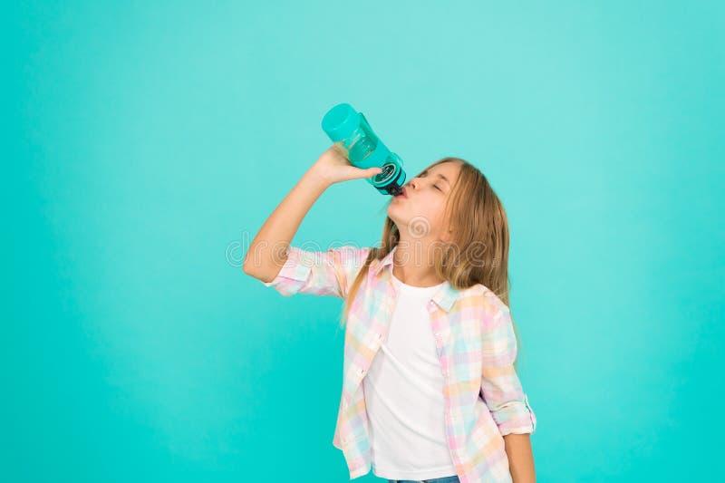 Blå bakgrund för ungehållflaska Begrepp för vattenjämvikt Sunt och hydratiserat Pediatriska oordningar av vattenjämvikt flicka royaltyfri foto