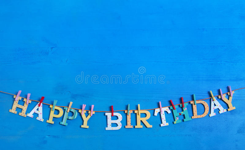 Blå bakgrund med färgrika trähängande bokstäver på en bekläda arkivbild