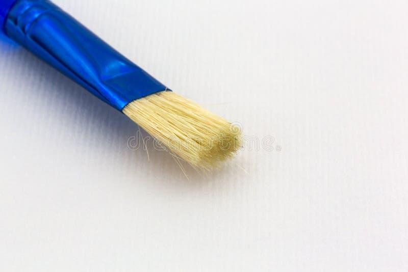 Blå borste uppe på texturerat vattenfärgpapper fotografering för bildbyråer