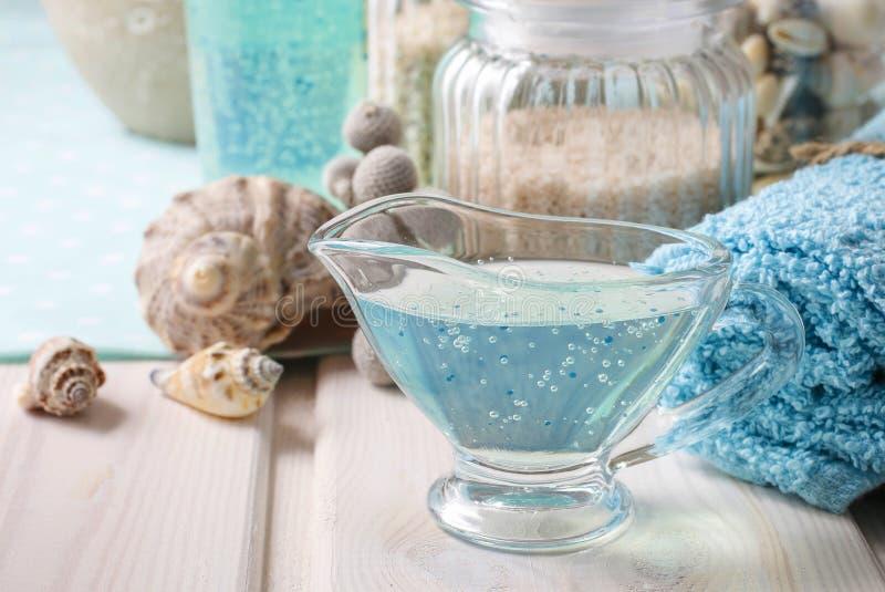 Blå brunnsortuppsättning: vätsketvål, havet saltar och handdukar arkivfoton