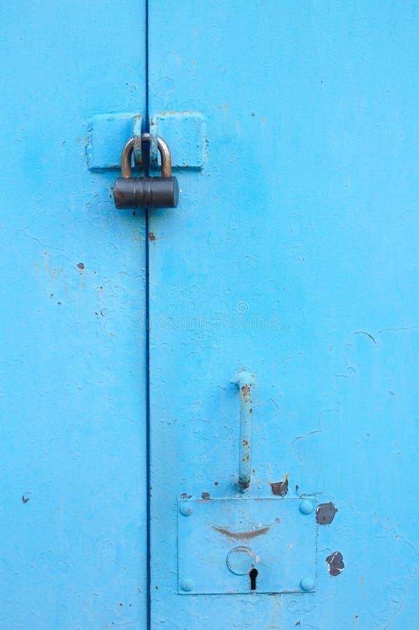 blå dörr för metall med hänglåset Gamla garageportar med nyckelhålet royaltyfria foton