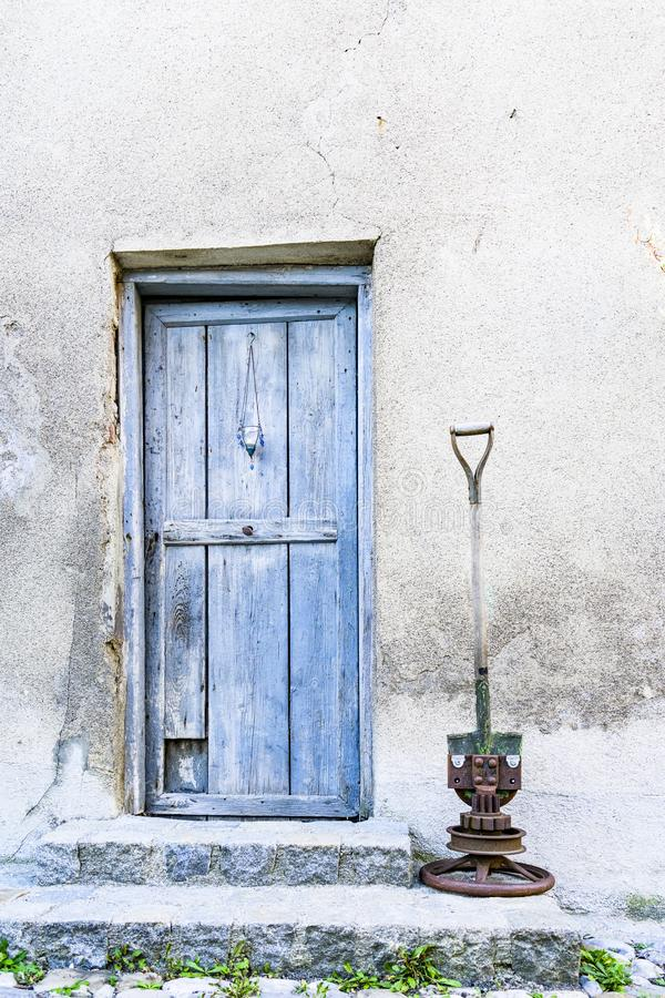 Blå dörr i bruten vit vägg royaltyfri bild