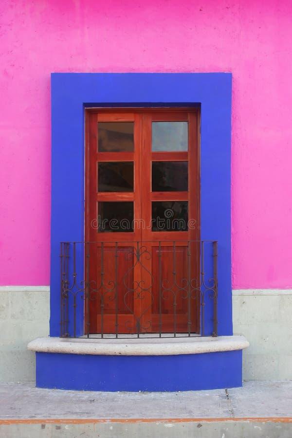 blå dörr inramning rosa vägg royaltyfria bilder