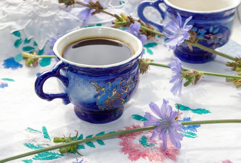 Blå drink för kopp kaffetecikoria med cikoriablomman, varm dryck på broderad tygbakgrund royaltyfri bild