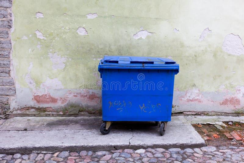 Blå dumpster mot ett ljust - grön vägg royaltyfria bilder