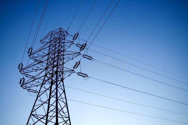 blå elektrisk lampa över pylonsilhouetteskyen royaltyfria foton
