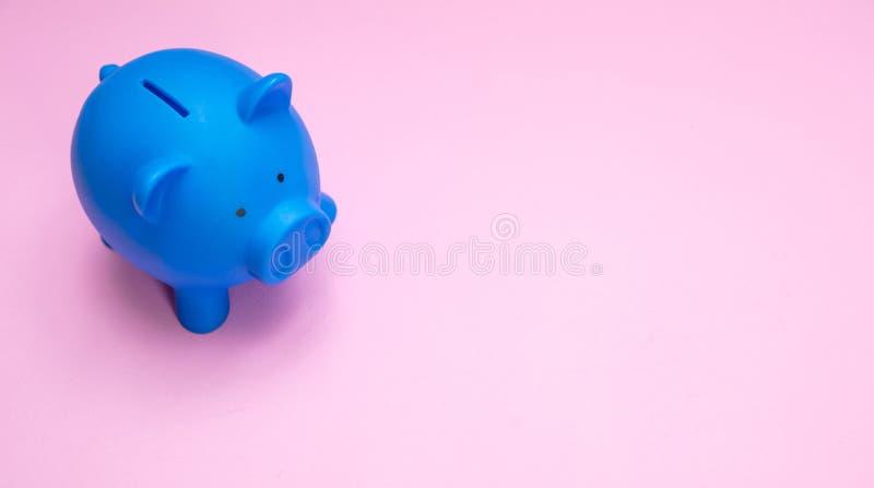 Blå färg för spargris mot pastellfärgad rosa bakgrund fotografering för bildbyråer