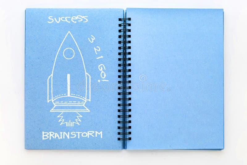 Blå färg skissar boken med begrepp för raketklotteridéer arkivfoto