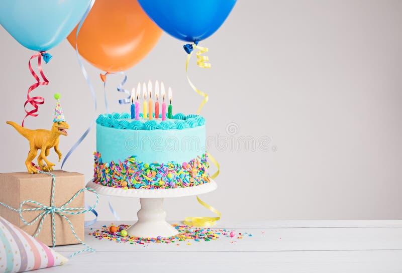 Blå födelsedagkaka med ballonger fotografering för bildbyråer