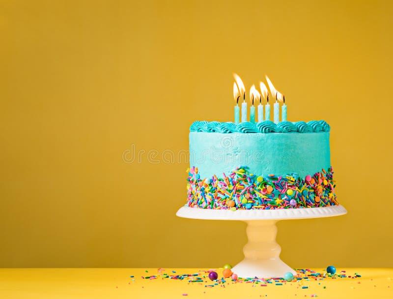 Blå födelsedagkaka på guling royaltyfria bilder