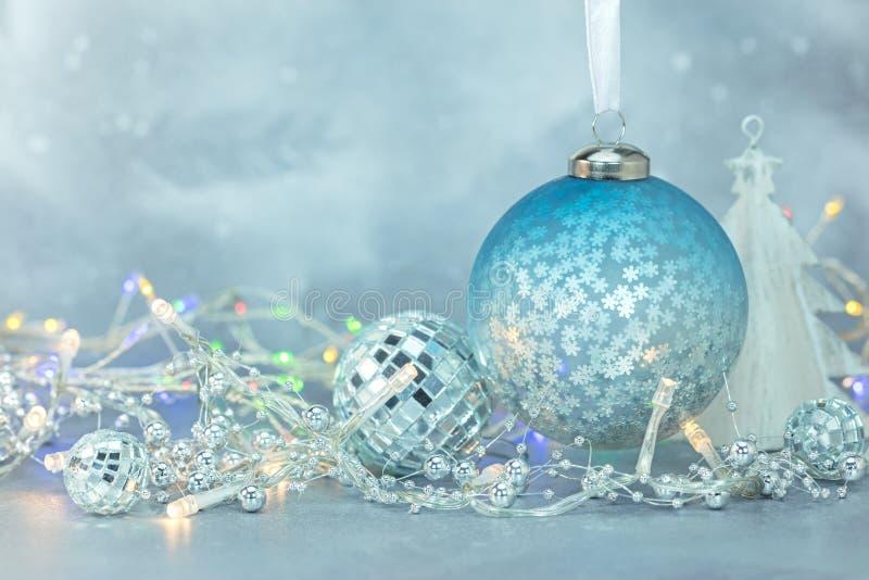Blå frostig vinterbakgrund med julprydnader och glowi arkivfoto
