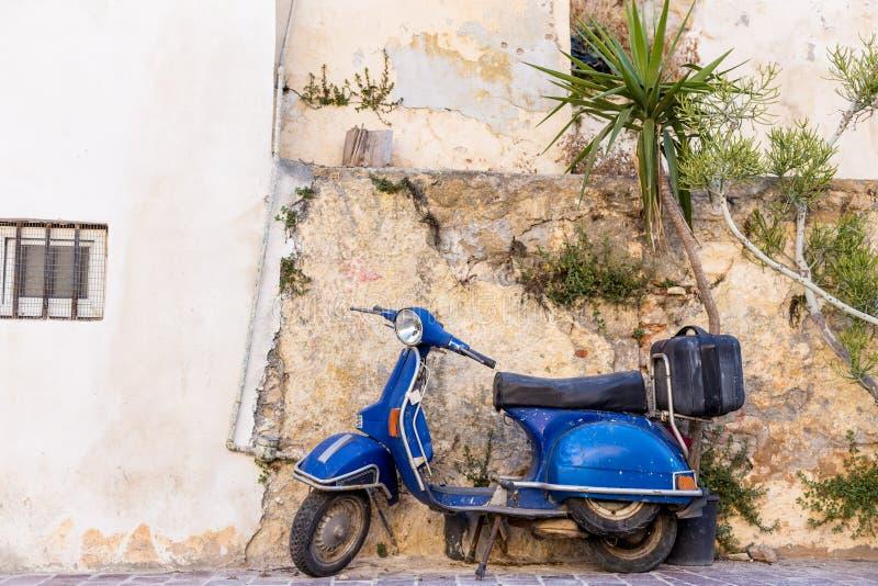 Blå gammal sparkcykel som parkeras av väggen i den tomma gataChania Kreta arkivfoton