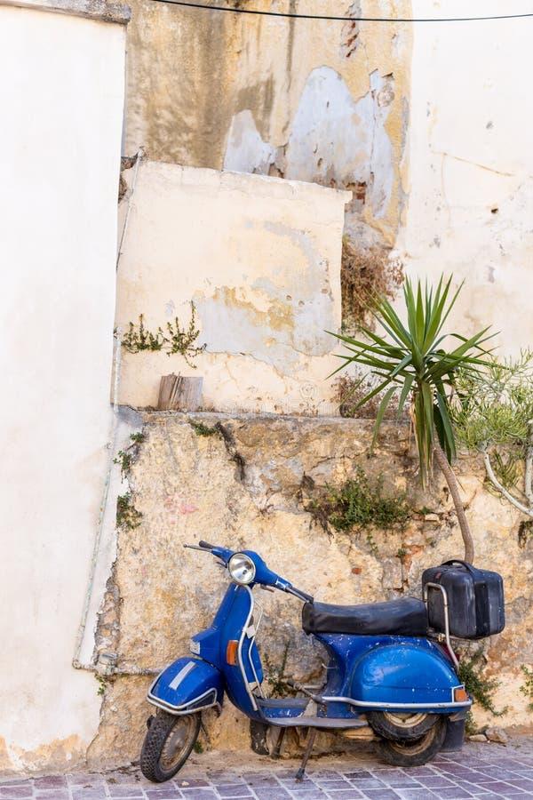 Blå gammal sparkcykel som parkeras av väggen i den tomma gataChania Kreta arkivbilder