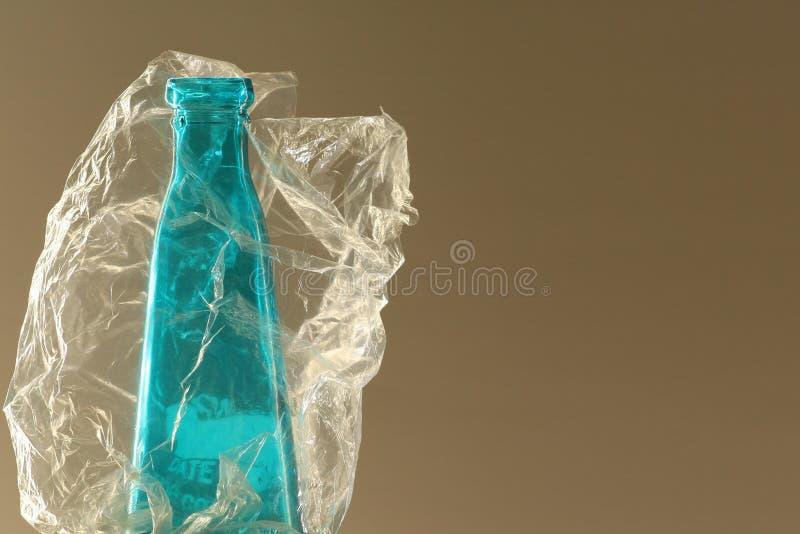 Blå glasflaska i klar plastpåse fotografering för bildbyråer