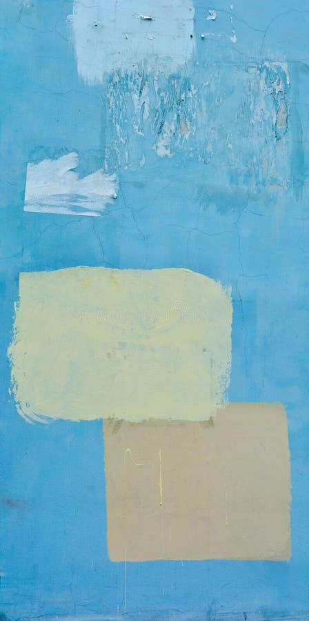 Blå grov betongvägg med sprickor och målade gula och orange fyrkanter royaltyfria bilder
