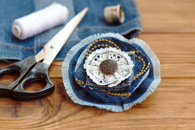 Blå grov bomullstvillblommabrosch eller hårtillbehör Sax tråd, fingerborg, visare, gammal jeans på en trätabell Återanvänt grov b royaltyfri fotografi