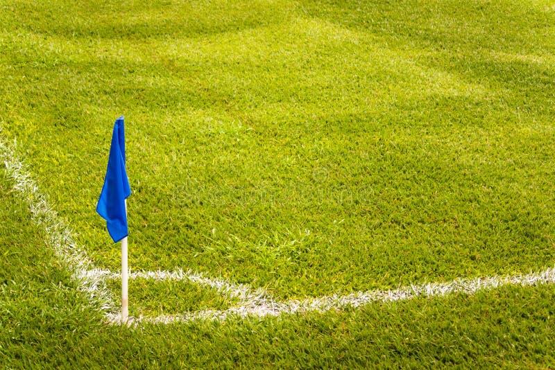 Blå hörnflagga på ett fotbollfält med grönt torvagräs royaltyfri foto