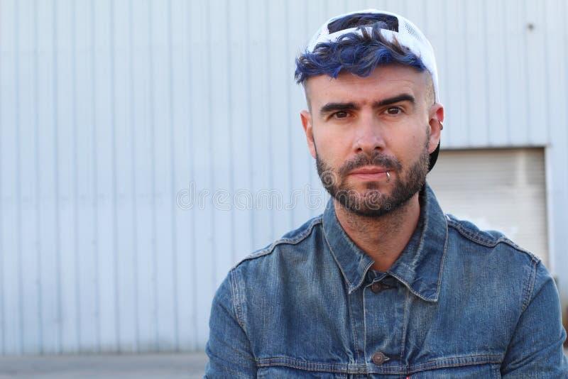 Blå haired trängd igenom moderiktig man som bär en baseballmössa med kopieringsutrymme arkivbild