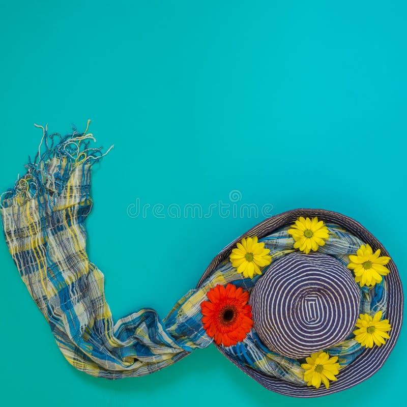 Blå hatt för sol som dekoreras med röda, gulingblommor och färgrika avskummar arkivfoton