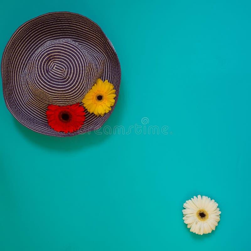 Blå hatt för sol som dekoreras med röda och gula blommor royaltyfria bilder