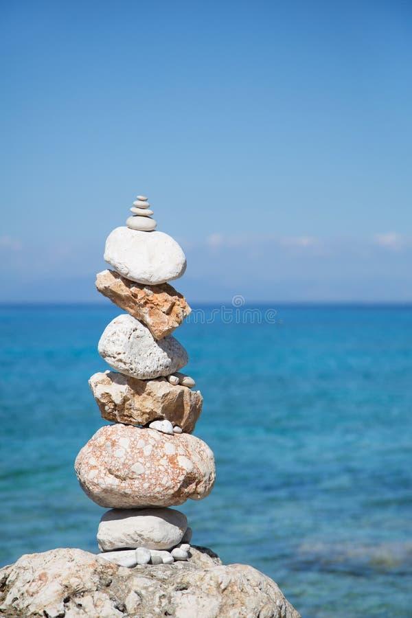 Blå havbakgrund med en pelare av stenar för meditativt eller arkivbilder