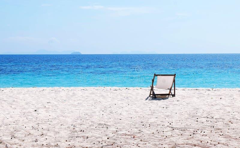 Blå havs- och vitsand med strandstolar arkivfoto