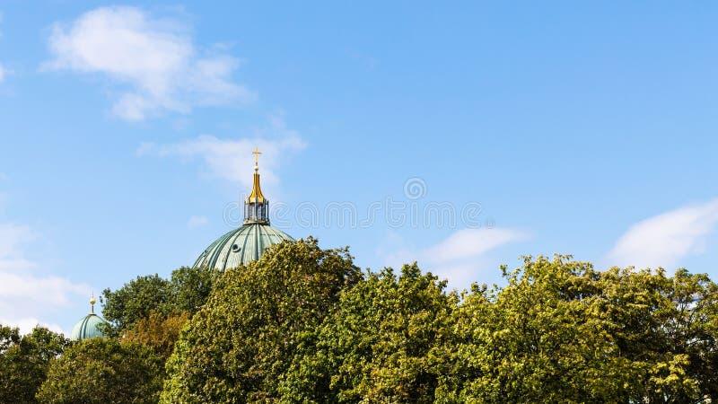 Blå himmel över grön lövverk och kupol av domkyrkan royaltyfri fotografi