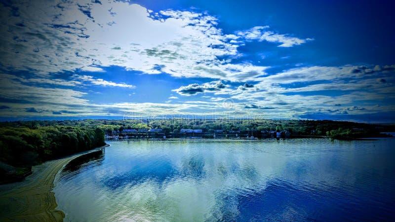 Blå himmel över vatten efter regnig dag royaltyfri fotografi