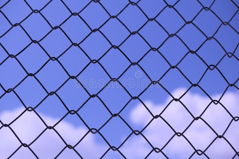Blå himmel bak trådgallret - abstrakt bakgrund royaltyfria bilder