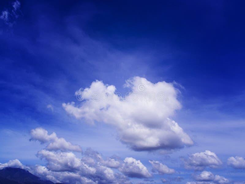 Blå himmel med det vita fluffiga molnet Mörk kontur för avlägset berg på ljus blå himmel royaltyfria foton