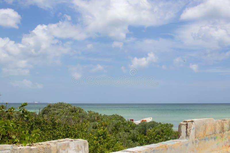Blå himmel med moln i Mexico beskådade över en delvist byggd betongvägg med havsgräs och delen av ett fartyg som var synligt nära royaltyfri bild