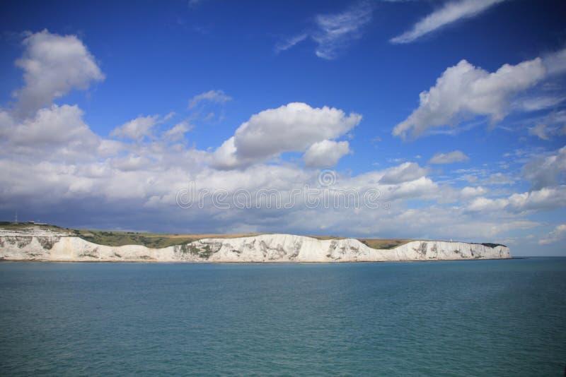 Blå himmel med moln och i avståndet Dover i England i sommaren royaltyfria foton
