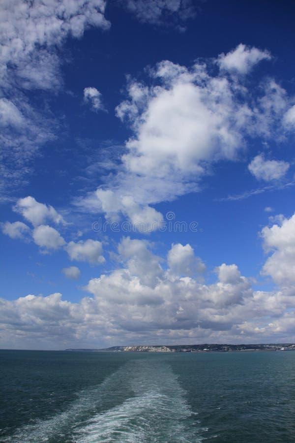 Blå himmel med moln och i avståndet Dover i England i sommaren arkivfoton
