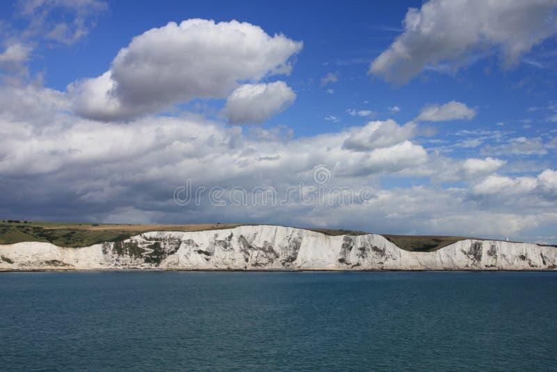 Blå himmel med moln och i avståndet Dover i England i sommaren arkivbilder