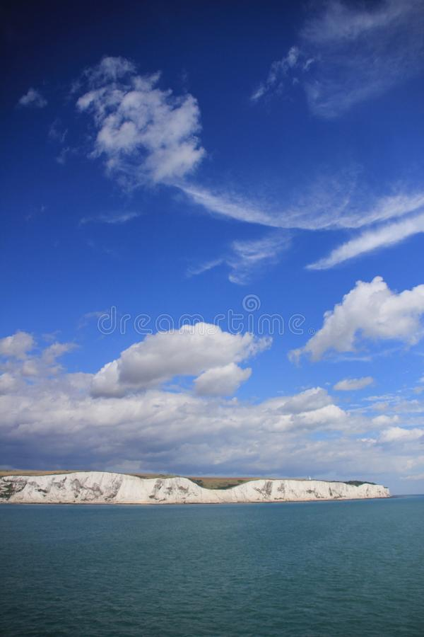 Blå himmel med moln och i avståndet Dover i England i sommaren royaltyfri foto