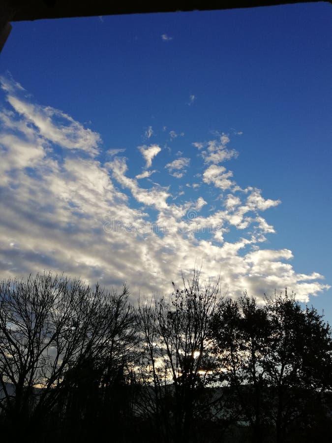 Blå himmel med små vita moln och stigningssolen royaltyfri foto