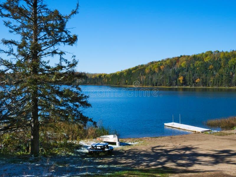 Blå himmel med solsken över den härliga fridfulla avlägsna nordliga Minnesota sjön arkivbild