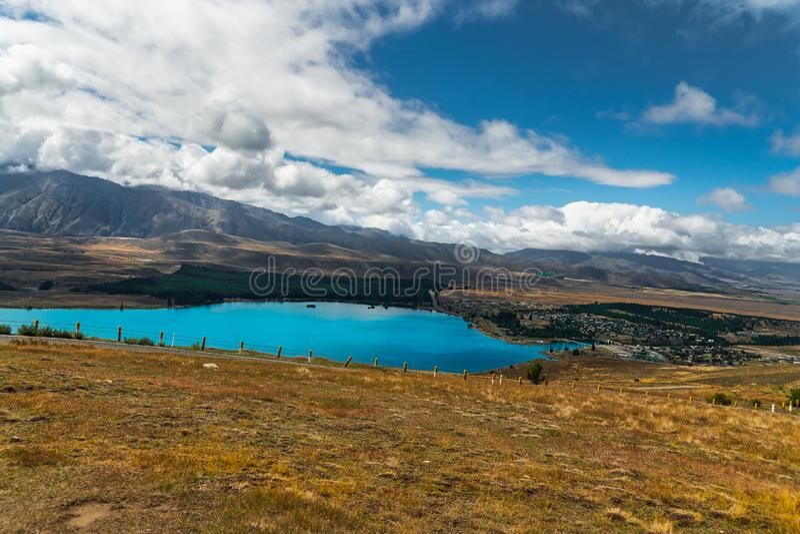 Blå himmel och bil Sjö Tekapo, berg och sjöTekapo by, Nya Zeeland arkivfoto