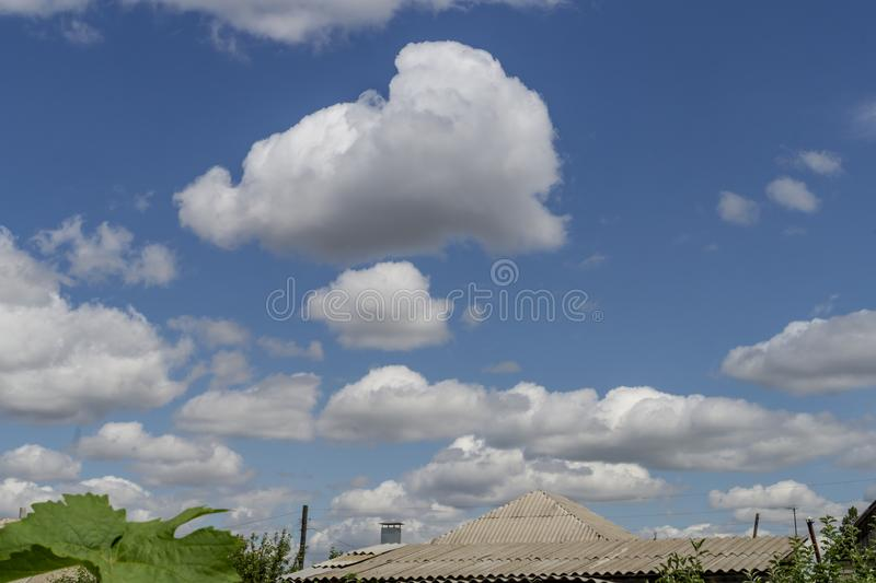 Blå himmel och härligt moln med tak av hus av byn Vanlig landskapbakgrund f?r sommaraffisch Den vidstr?ckta bl?a himlen royaltyfri fotografi