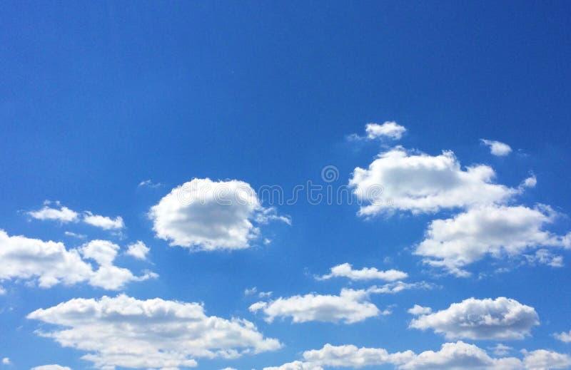 Blå himmel och vita pösiga moln fotografering för bildbyråer