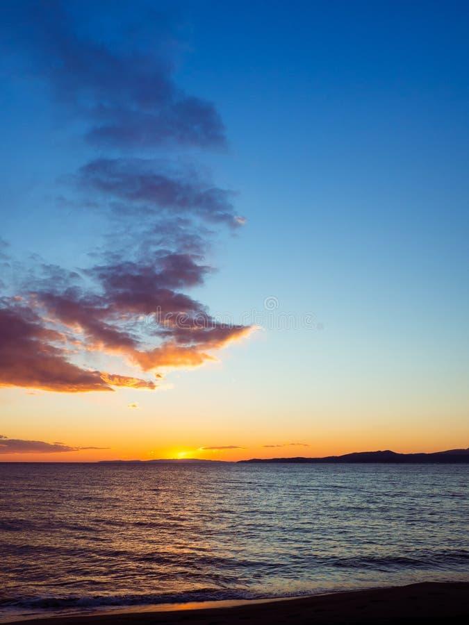 Blå himmel - orange vibrerande solnedgång över den lugna tomma stranden arkivfoto