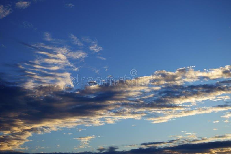 Blå himmel på en sommarsolnedgång med härliga moln fotografering för bildbyråer