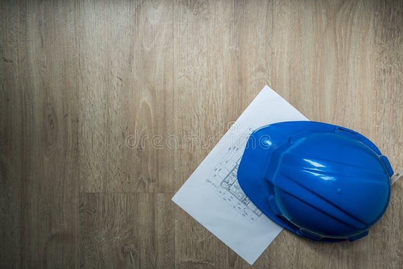 Blå hjälm för säkerhet och hem- konstruktionsplan i mörkerabstrakt begreppsignal, arkitektur eller industriella utrustningar, med royaltyfri foto