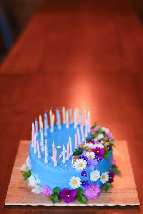 Blå isolerad kaka med stearinljus på träbakgrund med kopieringsutrymme royaltyfria bilder